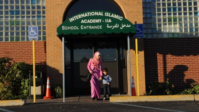 اماني راموني، تغادر الاكاديمية الاسلامية الدولية مع ابنها شادي، في ديترويت، 9 نوفمبر 2016 (AFP/Nova SAFO)
