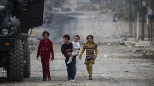 أطفال يخرجون من منازلهم لتحية جندي من الفرقة الثانية للقوات الخاصة العراقية خلال فترةهدوء في القتال مع مقاتلي تنظيم 'داعش' خلال الدخول إلى حي هدن في الموصل، 16 نوفمبر، 2016. (AFP PHOTO / Odd ANDERSEN)