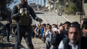 جندي من القوات الخاصة العراقية يجمع بطاقات الهوية من رجال تجمعوا في محافظة كركولي شرق الموصل، 18 نوفمبر 2016 (ODD ANDERSEN / AFP)