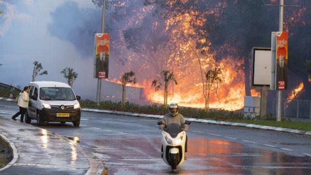 سائقون إسرائيليون يمرون أمام حريق مستعر في مدينة حيفا شمال إسرائيل، 24 نوفمبر، 2016. (Jack Guez/AFP)
