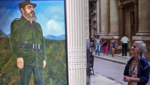 امرأة مسنة تنظر الى جدارية تظهر القائد الثوري الكوبي فيدل كاسترو في شوارع هفانا، 26 نوفمبر 2016 (ADALBERTO ROQUE / AFP)