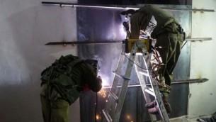 جنود إسرائيليون يغلقون ورشطة عمل يُزعم أنها استخدمت لصنع أسلحة غير قانونية في يطا، القريبة من الخليل، فجر 8 نوفمبر، 2016. (وحدة المتحدث بإسم الجيش الإسرائيلي)