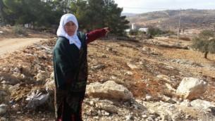 إمرأة فلسطينية تشير إلى الأرض التي تقول إنها كانت ملكا لعائلتها قبل أن تقوم إسرائيل بإنشاء مستوطنة عامونا في عام 1996، نوفمبر 2016. (Raphael Ahren/Times of Israel)