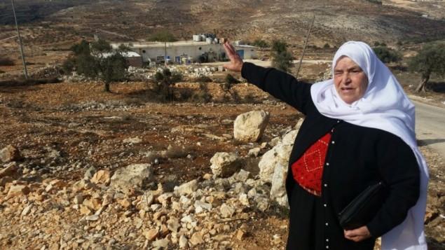 مريم حماد، من مدينة سلواد القريبة، تشير إلى قطعة أرض تقول إنها كانت ملكا لها قبل أن يقوم الإسرائيليون بالإستيلاء عليها وبناء مستوطنة عامونا، نوفمبر، 2016.  (Raphael Ahren/Times of Israel)