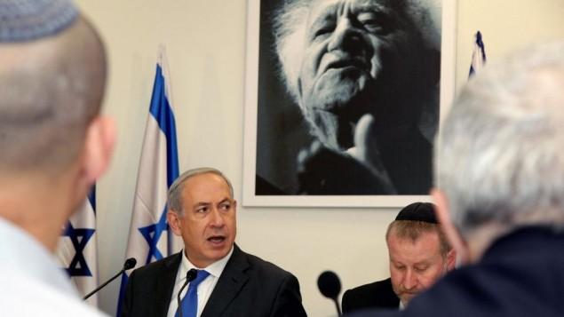 رئيس الوزراء يقف تحت صورة لرئيس الوزراء الإسرائيلي الأول دافيد بم غورويون خلال حديث له في جلسة خاصة للحكومة في أكاديمية 'سديه بوكر' لإحياء ذكرى مرور 40 عاما على وفاة بن غوريون. 10 نوفمبر، 2013. (Edi Israel/POOL/Flash90)