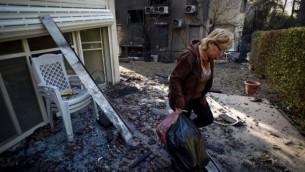 سيدة إسرائيلية تحمل بعضا من الأغراض من منزل محترق جراء حريق أحراش في مدينة حيفا الشمالية، إسرائيل في 25 نوفمبر، 2016. (Gili Yaari /Flash90)