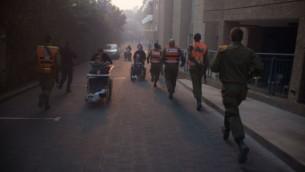 الجنود من قيادة الجبهة الداخلية التابعة للجيش الإسرائيلي يساعدون في عمليات الإخلاء في حيفا جراء حريق هائل أجتاح أجزاء من المدينة، 24 نوفمبر، 2016. (IDF Spokesperson's Unit)