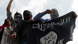 صورة توضيحية لرجال يحملون راية تنظيم الدولة الإسلامية (AFP/Tauseef Mustafa)