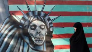 سيدة إيرانية تمر امام لوحة جدارية على جدارالمبنى السابق للسفارة الأمريكية في العاصمة الإيرانية طهران، 9 نوفمبر، 2016. (AFP/Atta Kenare)