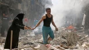 مواطنون يسيرون وسط ركام المباني المدمرة في أعقاب غارة جوية مزعومة على حي الكلاسة الذي يسيطر عليه المتمردون في في مدينة حلب شمال سوريا، 28 أبريل، 2016. (AFP PHOTO / AMEER ALHALBI)