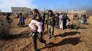 مدنيون سوريون يفرون من العنف ويتجمعون عند حاجز للقوات الموالية للنظام، في قرية عزيزة التي تقع جنوب غرب مدينة حلب في شمال سوريا، 8 ديسمبر، 2016. (AFP PHOTO / Youssef KARWASHAN)