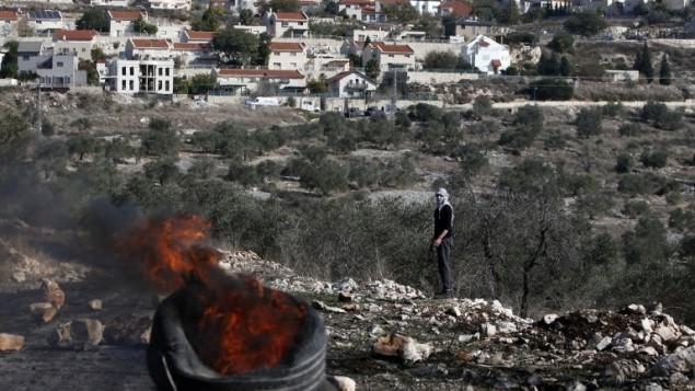 متظاهر فلسطيني ينظر الى اطارات مشتعلة خلال مواجهات مع قوات الامن الإسرائيلية بالقرب من مستوطنة كيدزميم في الضفة الغربية، 9 ديسمبر 2016 (AFP/JAAFAR ASHTIYEH)