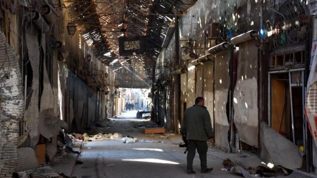 هذه الصورة تم إلتقاطها في 9 ديسمبر، 2016، ويظهر فيها مقاتل من القوات الموالية للنظام يمر بين المحال التجارية المغلقة في شارع باب النصر في البلدة  القديمة في مدينة حلب. (AFP PHOTO / George OURFALIAN)