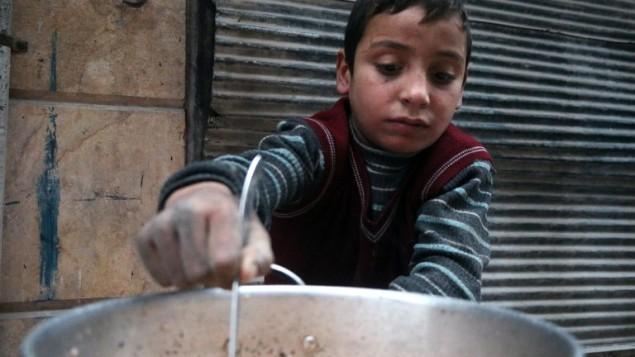 طفل سوري يطهو في الشارع المنطقة التي يسيطر عليها المتمردون في حلب في 13 ديسمبر، 2016 خلال العملية العسكرية التي تقوم بها قوات النظام السوري لإستعادة السيطرة على المدينة. (AFP PHOTO / STRINGER)