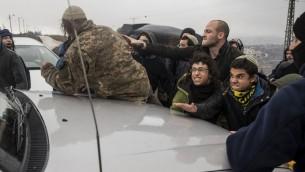 مستوطنون يحاولون سد الطريق امام سيارة تنقل وزير الاسكان يؤاف غالانت، في بؤرة عامونا الاستيطانية في الضفة الغربية، 18 ديسمبر 2016 (AFP /JACK GUEZ)
