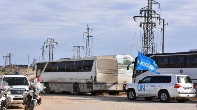 حافلات تمر عبر معبر راموسة الذي تسيطر عليه قوات النظام، على المشارف الجنوبية لمدينة حلب، 18 ديسمبر، 2016، خلال عملية إجلاء لمقاتلين من المعارضة ومدنيين من المناطق التي يسيطر عليها المتمردون. (AFP PHOTO / George OURFALIAN)