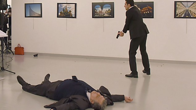 """This picture taken on December 19, 2016 shows Andrey Karlov (L), the Russian ambassador to Ankara, lying on the floor after being shot by a gunman (R) during an attack during a public event in Ankara. A gunman crying """"Aleppo"""" and """"revenge"""" shot Karlov while he was visiting an art exhibition in Ankara on December 19, witnesses and media reports said. The Turkish state-run Anadolu news agency said the gunman had been """"neutralised"""" in a police operation, without giving further details. / AFP PHOTO / Sozcu daily / Yavuz Alatan / Turkey OUT"""