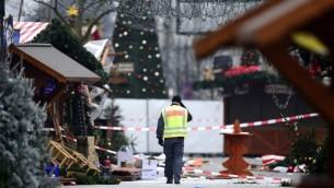 شرطي يمشي في سوق عيد ميلاد في برلين اقتحمته شاحتة، ما ادى الى مقتل عدة اشخاص واصابة العشرات، 20 ديسمبر 2016 (TOBIAS SCHWARZ / AFP)