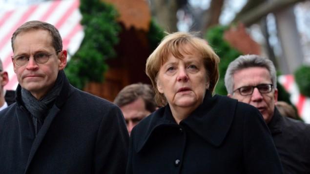 المستشارة الالمانية انغيلا ميركل ورئيس بلدية برلين ميكايل مولير، بزيارة الى موقع دهس بشاحنة في سوق عيد ميلادي في برلين، 20 ديسمبر 2016 (AFP PHOTO/DPA/Maurizio Gambarini)