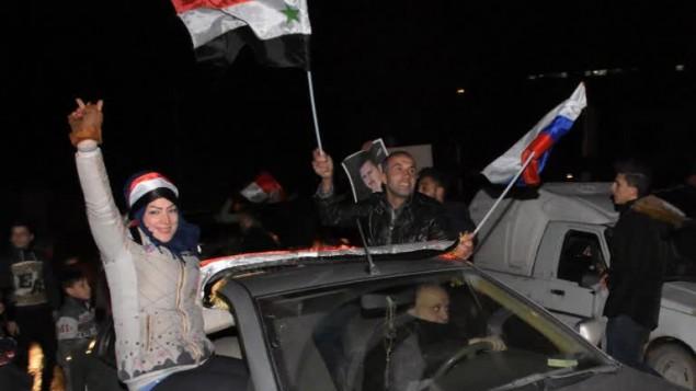سوريون يلوحون بالاعلام السورية والروسية في شوارع حلب احتفالا بسيطرة قوات النظام السوري على المدينة، 22 ديسمبر 2016 (GEORGE OURFALIAN / AFP)