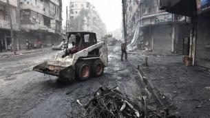 جرافة تزيل الحطام مع ابتداء الحكومة التنظيفات في مدينة حلب الشمالية، 27 ديسمبر 2016 (AFP/George Ourfalian)