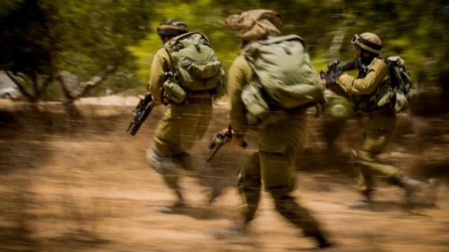 صورة للتوضيح: جنود يهرعون باتجاه هدف خلال حرب غزة في عام 2014، التي تُعرف في إسرائيل بإسم 'عملية الجرف الصامد'، 4 أغسطس، 2014. (وحدة المتحدث بإسم الجيش الإسرائيلي)