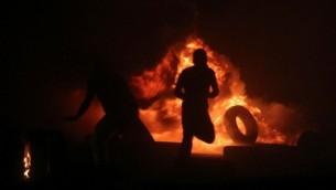 صورة توضيحية: رجال فلسطينيون يقومون بحرق الإطارات خلال مواجهات مع شرطة حرس الحدود الإسرائيلية عند حاجز قلنديا، بين القدس ورام الله، 24 يوليو، 2014. (Issam Rimawi/Flash90)