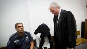 بن ديري (وسط الصورة)، المتهم بقتل شاب فلسطيني يبلغ من العمر 20 عاما من خلال إستخدامه للرصاص الحي خلال مواجهات في بيتونيا في الضفة الغربية، مع محامية تسيون عمير (من اليمين)، خلال جلسة في المحكمة المركزية في القدس، 7 ديسمبر، 2014. (Miriam Alster/Flash90)