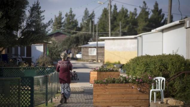 إحدى سكان يؤرة عامونا الإستيطانية غير القانونية في الضفة الغربية، تظهر في الصورة وهي تسير في شوارع المستوطنة في 17 نوفمبر، 2016.(Miriam Alster/Flash90)