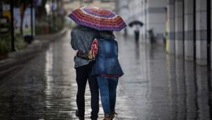 صورة توضيحية لزوج يمشيان تحت المطر في تل ابيب، 1 ديسمبر 2016 (Nati Shohat/Flash90)