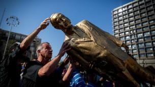اسقاط تمثال ذهبي لرئيس الوزراء بنيامين نتنياهو في ميدان رابين بتل ابيب، 6 ديسمبر 2016 (Miriam Alster/Flash90)