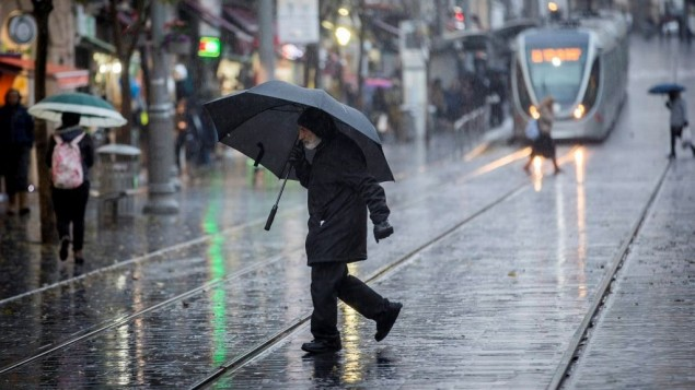 اشخاص يمشون تحت المطر في شارع يافا بالقدس، 14 ديسمبر 2016 (Yonatan Sindel/Flash90)