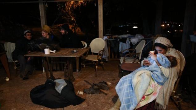 عائلات تجلس أمام منزل في بؤرة عامونا الإستيطانية في الضفة الغربية، 17 ديسمبر، 2016. (Miriam Alster/Flash90)