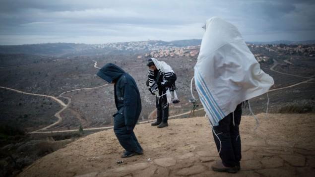 رجال يهود يصلون في ساعات الصباح الباكر في بؤرة عامونة الاستيطانية، التي تطل على مستوطنة عوفرا في الضفة الغربية، 18 ديسمبر 2016 (Miriam Alster/Flash90)