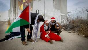 متظاهرين فلسطينيين يرتدون زي بابا نويل خلال مظاهرة ضد الجدار الامني الإسرائيلي في بيت لحم، 23 ديسمبر 2016 (Wisam Hashlamoun/FLASH90)