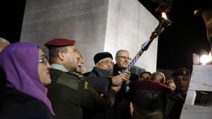 رئيس السلطة الفلسطينية محمود عباس يضيء شعلة للاحتفال في الذكرى ال52 لتأسيس حركة فتح، في مدينة رام الله في الضفة الغربية، 31 ديسمبر 2016 (AFP/Abbas Momani)