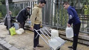 سوريون يعبؤون اوعية بلاستيكية بالمياه من حنفية عامة في العاصمة السورية دمشق، 3 يناير 2017 (LOUAI BESHARA / AFP)