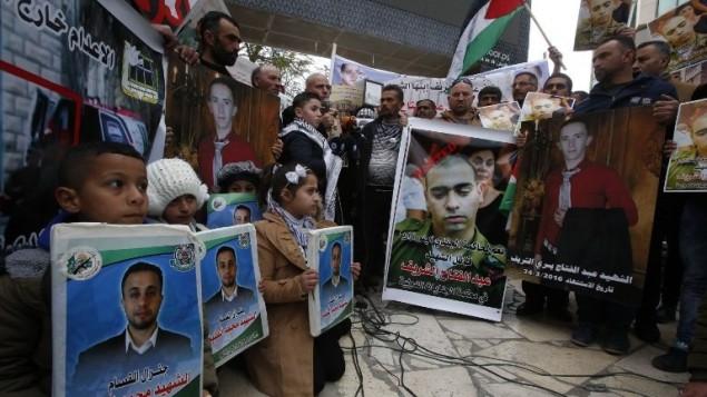 فلسطينيون يحملون ملصقات خلال مظاهرة في مدينة الخليل بالضفة الغربية، اثناء صدور الحكم ضد الجندي الإسرائيلي ايلور عزاريا الذي قتل عبد الفتاح الشريف، 4 يناير 2017 (AFP/HAZEM BADER)