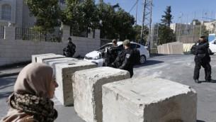 قوات أمن إسرائيلية تقف إلى جانب حاجز إسمنتية تم وضعها حديثا في حي جبل المكبر في القدس الشرقية، 9 يناير، 2017. (AFP/AHMAD GHARABLI)