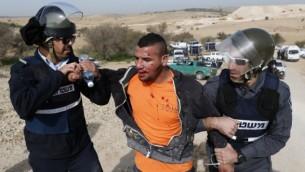 الشرطة الإسرائيلية تعتقل شابا بدويا خلال احتجاجات ضد هدم المنازل في 18 يناير، 2017، في قرية أم الحيران البدوية الغير معترف بها في النقب. (AFP Photo/Ahmad Gharabli)
