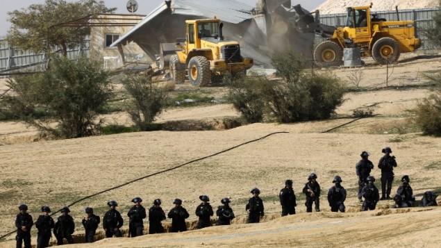 رجال الشرطة يحرسون الجرافات اثناء عمليات الهدم في قرية ام الحيران في النقب في 18 يناير، 2017 AFP PHOTO / MENAHEM KAHANA