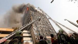 """رجال اطفاء يحاول اخماد حريق في اقدم برج في طهران، مبنى """"بلاسكو""""، قبل انهياره، 19 يناير 2017 (STR, HO / AFP)"""