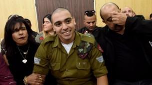 الجندي الإسرائيلي إيلور عزاريا، الذين أدين بالقتل غير العمد لمنفذ هجوم فلسطيني، في القضية التي أثارت انقساما عميقا في المجتمع الإسرائيلي، مع والديه في انتظار جلسة استماع في المحكمة العسكرية في تل أبيب، 24 يناير، 2017. (AFP/DEBBIE HILL)