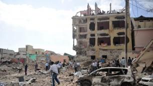 أشخاص يسيرون بين الركام في أعقاب هجوم وقع أمام فندق في 25 يناير، 2017، في مقديشو.  (AFP PHOTO / MOHAMED ABDIWAHAB)