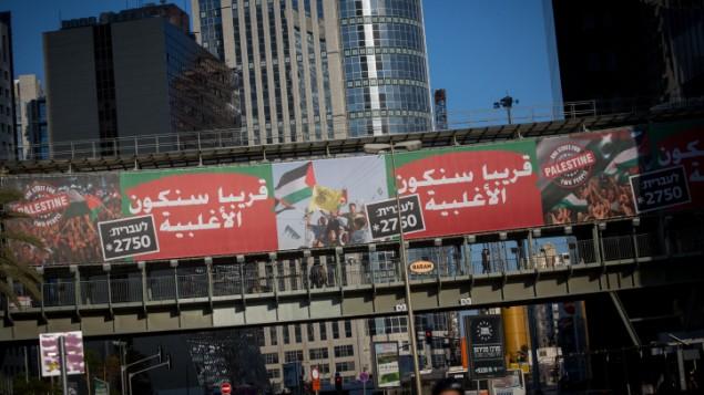 حملة إعلانية لمنظمة 'قادة من أجل أمن إسرائيل' تشمل لوحات إعلانية يظهر فيها العلم الفلسطيني، مع رسالة، 'دولة واحد لشعبين - فلسطين'. إحدى هذه اللوحات الإعلانية تم وضعها على طرق آيالون السريع وسط تل أبيب، 15 يناير، 2017. (Miriam Alster/Flash90)