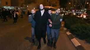 خلال تظاهرة ضد سجن طالبة معهد ديني لم تمتثل لأمر تجنيدها، الشرطة تعتقل رجل حريدي، في بيت شيمش، 17 يناير، 2017. (Yaakov Lederman/Flash90)