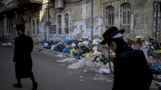 رجال يهود متشددون  يمرون يجانب اكوام من النفايات ناتجة عن اضراب بلدية القدس في حي مئا شعارين، 30 يناير 2017 (Yonatan Sindel/Flash90)