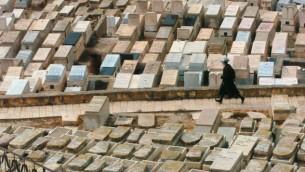 صورة للتوضيح: رجل يسير في مقبرة في القدس في صورة غير مؤرخة من الأرشيف. (Nati Shohat /Flash90)