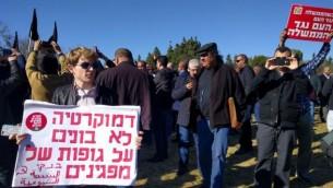 """ناشط يحمل لافتة كُتب عليها، """"لا يمكن أن تقوم الديمقراطية على جثث متظاهرين'، خلال تظاهرة ضد هدم المنازل في الوسط العربي، أمام الكنيست في القدس. 23 يناير، 2017. (courtesy Joint List)"""