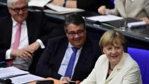 المستشارة الألمانية أنغيلا ميركل (من اليمين) ووزير خارجيتها سيغمار غابرييل (في الوسط) والمرشح الرئتسي فرانك فالتر شتاينماير  في البوندستاغ في برلين، 7 يوليو، 2016.  (AFP photo/John MacDougall)